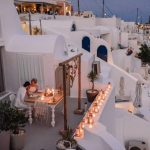 Couple having a private candlelit dinner on a patio in Greece