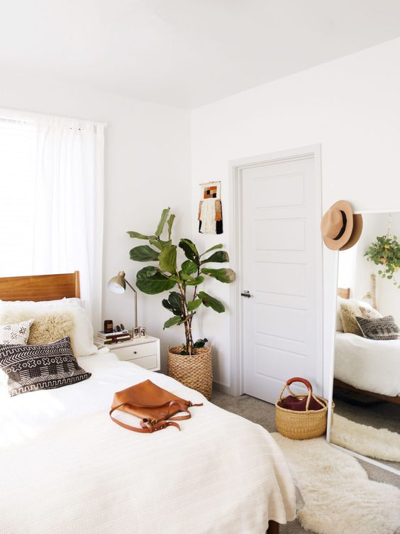 White bedroom with white bedding and a big plant sitting on the floor in a woven baskey