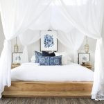Large bed with white bedding, blue throw pillows, blue reef artwork and a white fabric canopy over the bed.