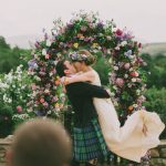 Bride and groom kissing in front of a flower archway
