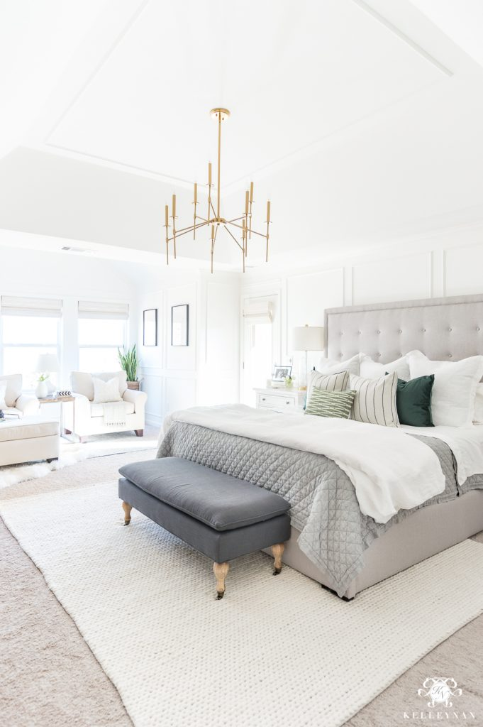 Light filled bedroom with white walls and bedding, a grey headboard and comforter, and green throw pillows