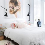 White bedroom with pink pillows and painting of a girl with flowers in her hair above the bed