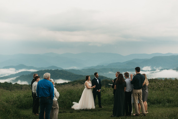 bride and groom on top of a mountain with 10 people attending the wedding