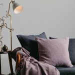 Charcoal grey couch with lavender throw pillows and a throw blanket