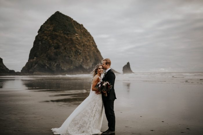 bride and groom standing on a dark beach in Orgeon