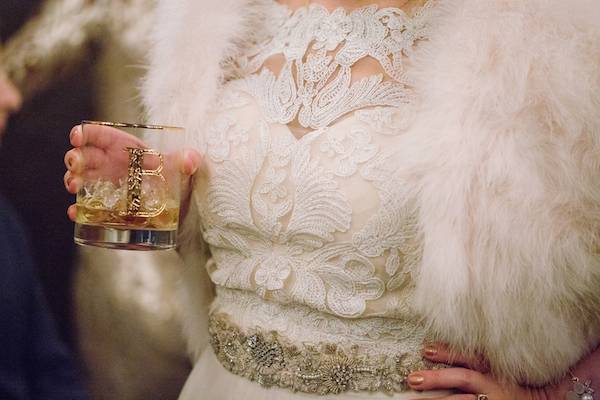 Close up of intricate lace Art Deco gown and a hand holding a golden plated cocktail glass