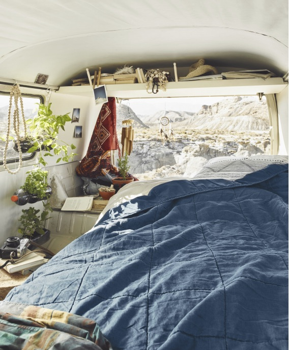 a bed in the back of a VW van, looking out over the wilderness with a navy blue comforter.