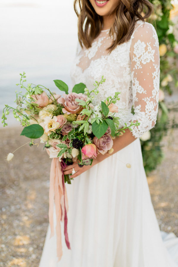 Bride in intricate lace gown and a large bouquet of flowers