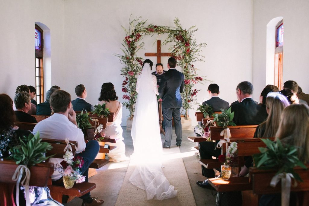 Bride and groom in small chapel with a few friends and family