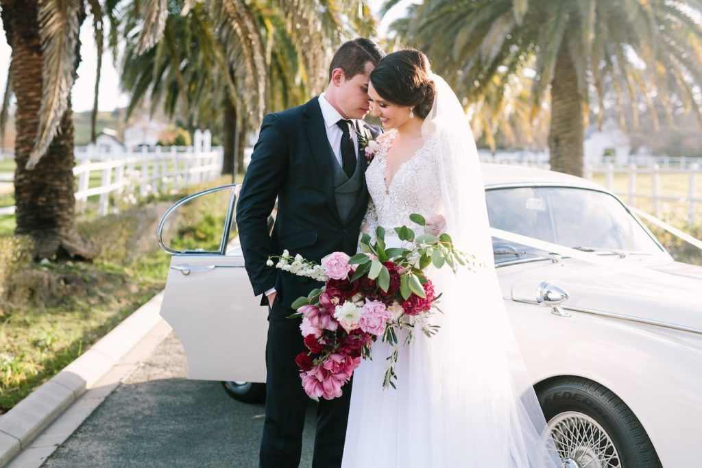 Bride and groom standing in front of classic car