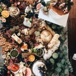 large table filled with various meat, cheese, breads, and fruit