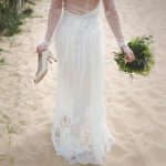 the back of a woman walking on the beach wearing a wedding dress and holding her shoes in her hand