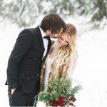 bride and groom in the snow. Bride wearing a lace white gown with a fur vest over it and carrying red roses