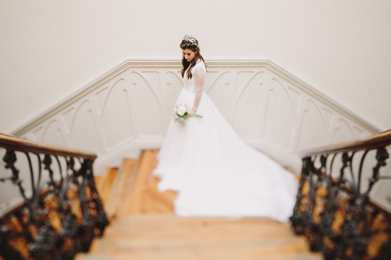 Bride standing at the bottom of a flight of stairs wearing a very simple long sleeved wedding gown with a large train