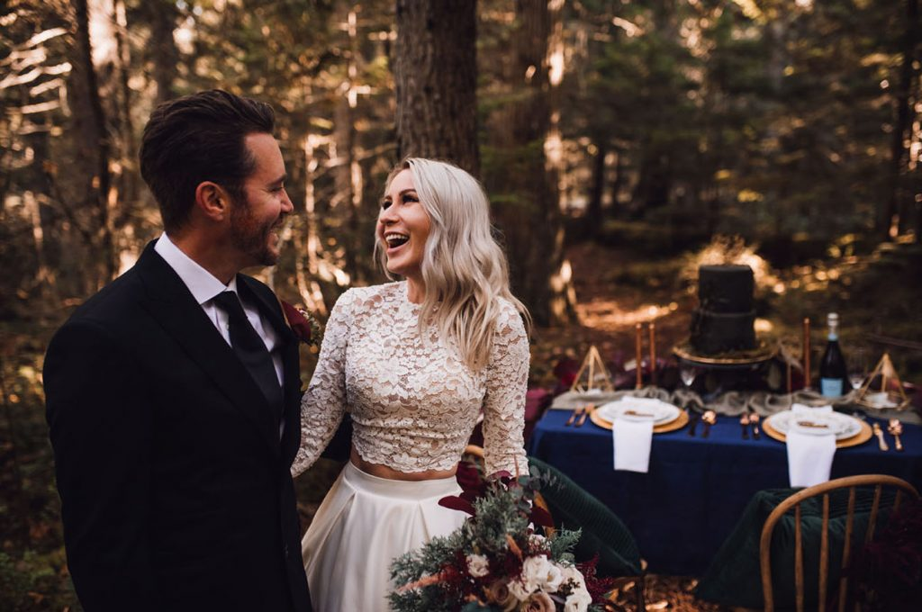 bride and groom standing in the forest. The bride is wearing a two piece dress with a long sleeved lace bodice