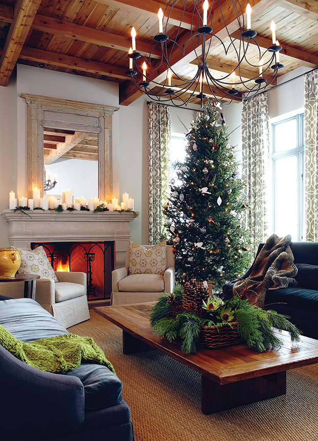 a photo of a living room with a large Christmas tree and fireplace with candles and faux fur throw blankets
