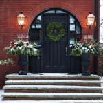 the exterior of a red brick home and a large green leaf wreath and two large planters on either side of the door