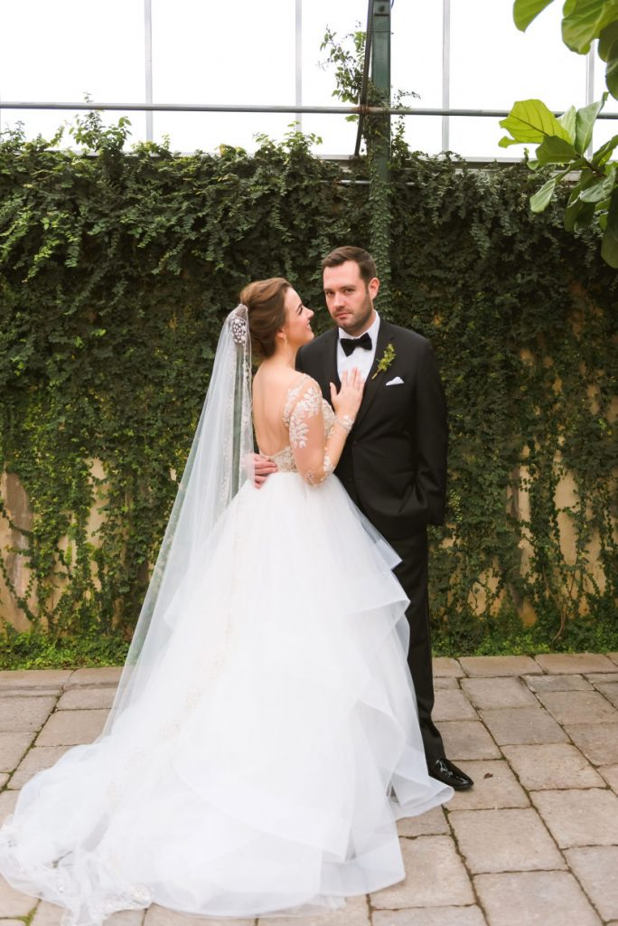 Bride and groom in a botanical garden. Groom is wearing a tux and a bow tie. Bride is wearing a tulle skirt and a lace long sleeved bodice.