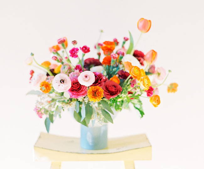 Large wild looking flower arrangement in a vase featuring ranunculus
