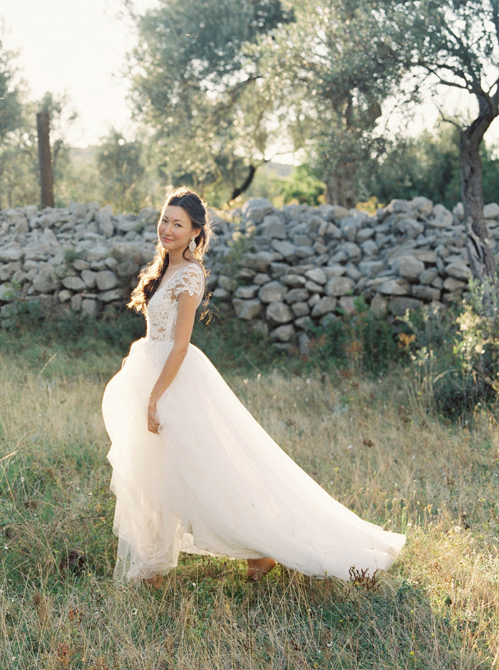 Bride standing in a field with a stone wall behind her. The dress has floral lace on the top and a tulle skirt