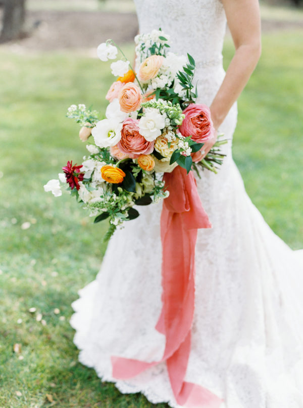 Woman from the neck down in a white lace wedding dress holding a large cascading bouquet of spring flowers