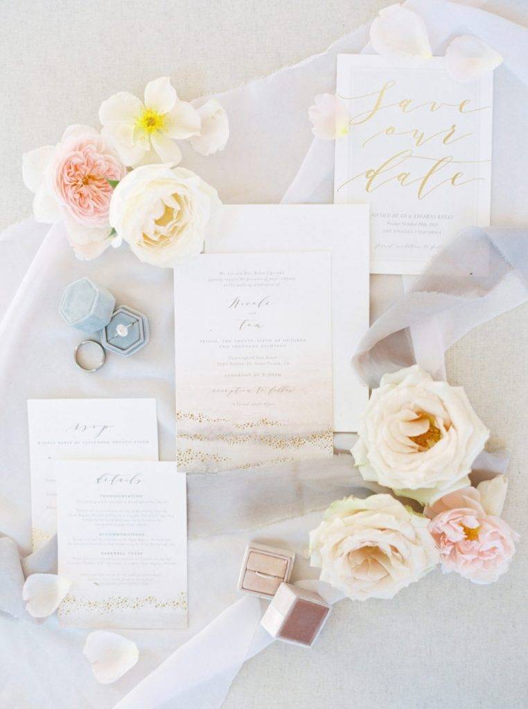 A series of floral wedding invitations displayed with flowers around them