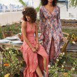 Two women standing in a rooftop garden wearing long flowing dresses