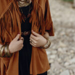 Woman wearing a camel suede jacket with fringe. Have you wondered if suede is durable? Here's how to wear it and keep it clean.